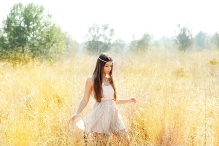 yellow dress: Asian indian woman walking in golden dried grass field Stock Photo