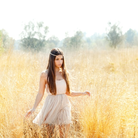 spring fashion: Asian indian woman walking in golden dried grass field Stock Photo