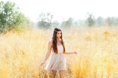 Asian indian woman walking in golden dried grass field photo