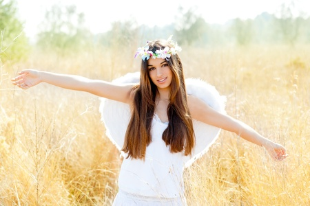 Angel etchnic woman in golden field with feather white wings and flowers crown photo