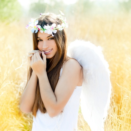 angels: Angel etchnic woman in golden field with feather white wings and flowers crown