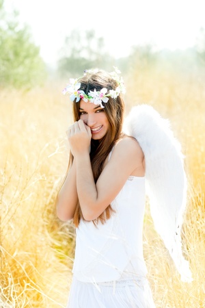 asian angel: Angel etchnic woman in golden field with feather white wings and flowers crown