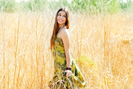 country girl: Asian indian woman walking outdoors in golden field with green long dress