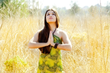 Asian indian woman praying hands  in golden field with green dress photo