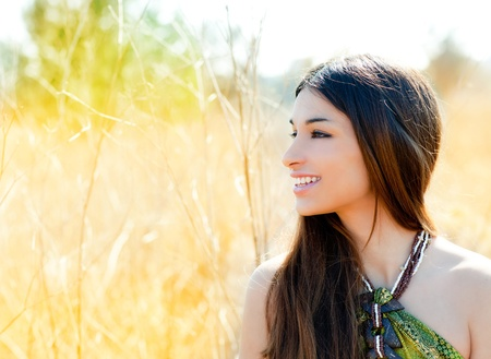 couture: Asian indian woman profile portrait in golden grass field