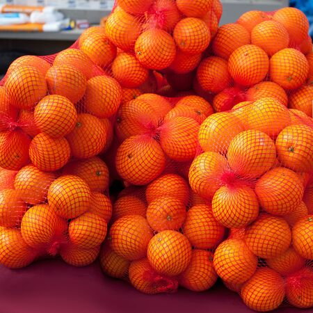 oranges fruit on market in red net bags photo