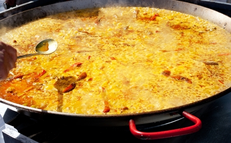 Paella rice typical from Valencia Spain cooking in big pan photo