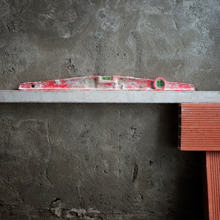 bubble spirit level tool in red on costruction cement wall with bricks photo