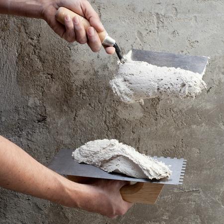vijzel: bouw lijmkam en werknemer handen met witte mortel op muur