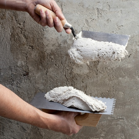 construction notched trowel and worker hands with white mortar on wall photo