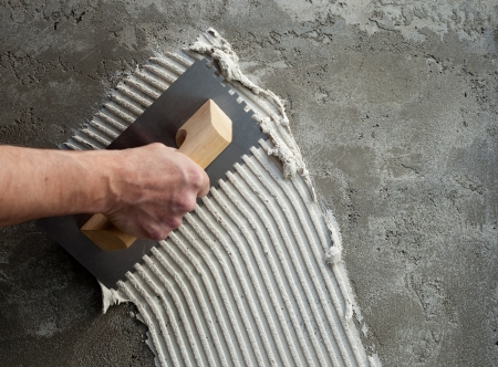 construction notched trowel with white cement mortar for tiles work photo