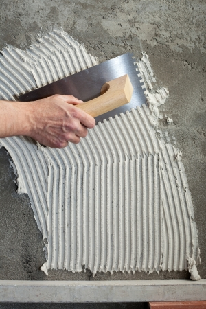 notched: construction notched trowel with white cement mortar for tiles work Stock Photo