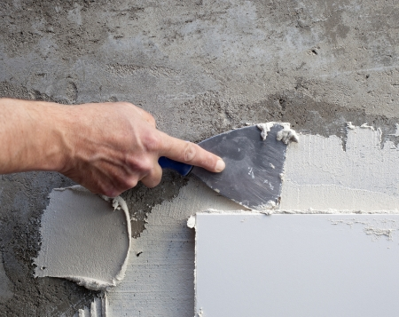 placing: construction spatula trowel in tile work with white mortar