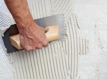 trabajo manual: la construcción de la llana con mortero de cemento blanco para el trabajo azulejos