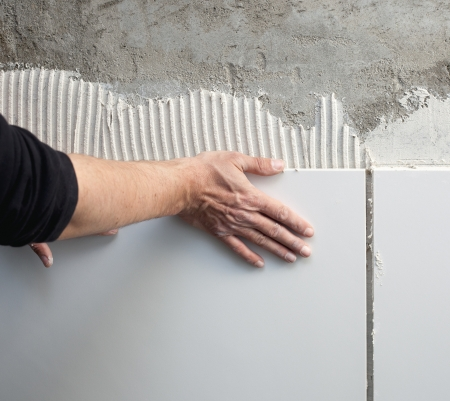 tegelwerk: bouw metselaar man handen op tegels te werken met een getande lijmkam cementmortel Stockfoto