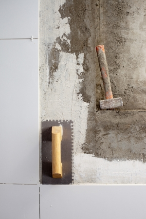 construction tools notched trowel and hammer on tiles mortar wall photo