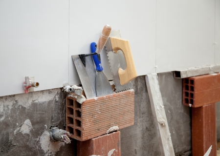 construction tools notched trowel ans spatula on tiles mortar wall photo