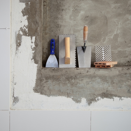 construction stainless steel trowel tools and spatula on cement mortar wall photo