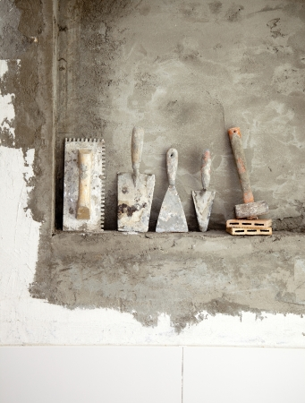 notched: aged construction cement used tools grunge on mortar wall Stock Photo