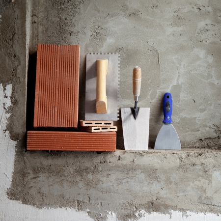 construction stainless steel trowel tools and bricks on cement mortar wall photo