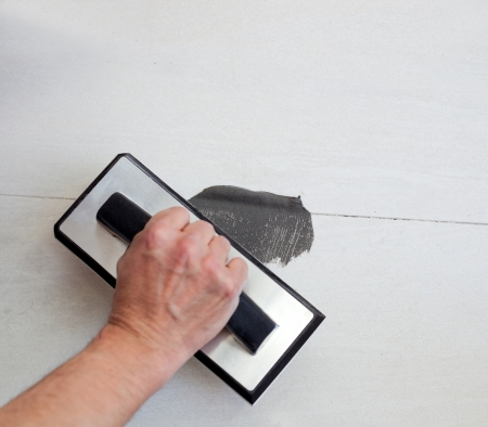 grouting tiles with rubber trowel and gray cement mortar photo