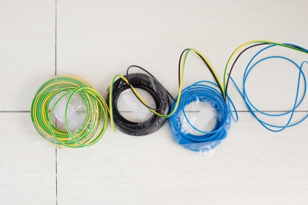 electrical wire: Electric cable coil in three colors black blue and green yellow earth ground