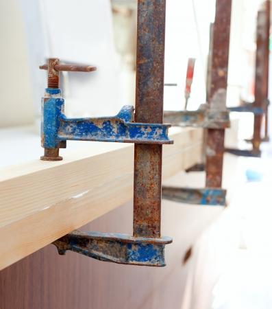 Carpenter screw clamp tools pressing wood slats ang white glue Stock Photo