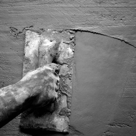 plastering: dirty trowel with glove hand plastering cement mortar in the wall Stock Photo
