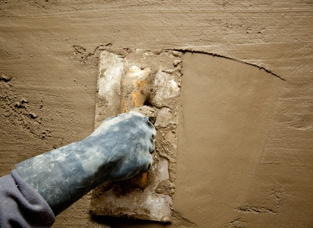 dirty trowel with glove hand plastering cement mortar in the wall photo