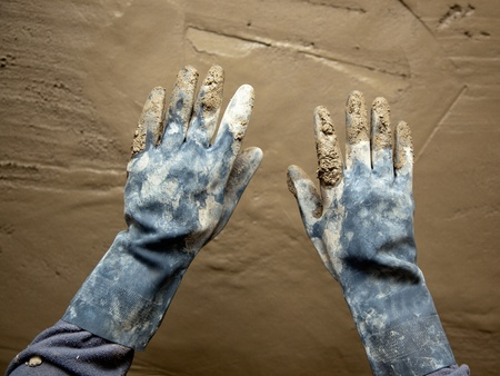 dirty grunge gloves hands on cement mortar fresh wall photo