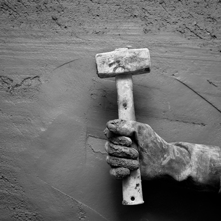 hammer man hand with gloves in grunge cement mortar background photo