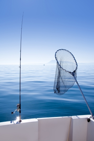 trolling: boat fishing rod and landing net in mediterranean blue sea