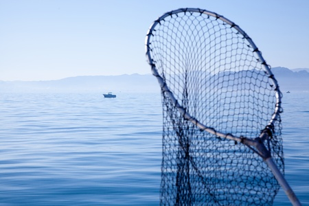 landing light: fishing landing net in blue sea at Mediterranean Stock Photo