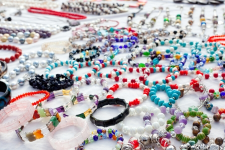 jewelry mixed in a bargain market spread on white fabric photo