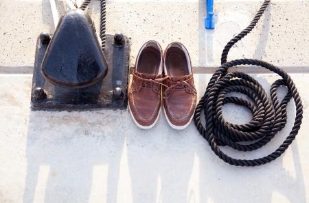 calzado de seguridad: Bolardo con zapatos náuticos y la bobina de cable de barco en el puerto