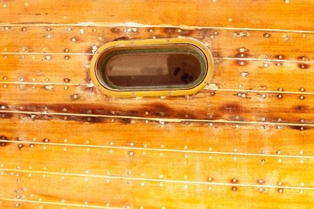 caulk: boat oval aged brass porthole in wooden hull with caulking putty and screw Stock Photo
