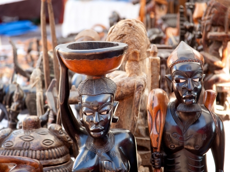 african mask: african handcraft dark wood carved people figures Editorial