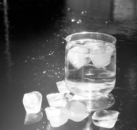 floating on water: ice cubes on an iced water surface and cup glass Stock Photo