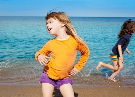 Blond kid girl dancing on the beach and her friend running on shore photo