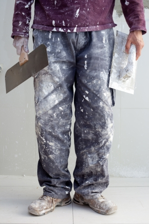 construction plastering man dirty trousers with trowel in hand photo