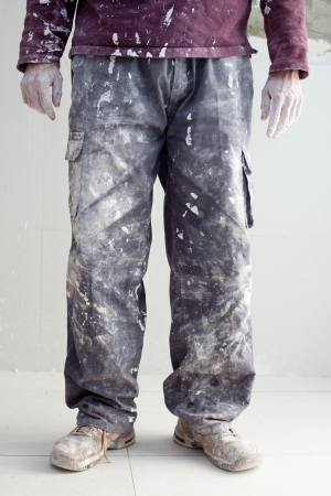 dirty man: hands and white dirty trousers detail of plastering painter man Stock Photo