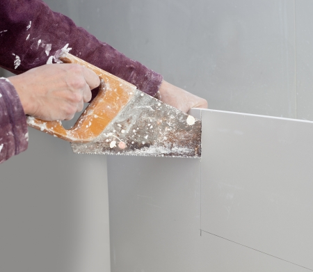 cutting plasterboard plaster hand with grunge dirty saw photo