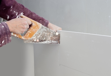 gypsum: cutting plasterboard plaster hand with grunge dirty saw
