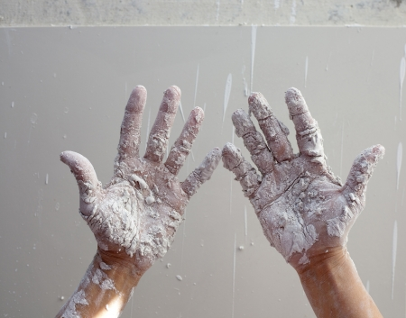 Astist plastering man hands with white dried cracked plaster texture in fingers Stock Photo - 13601476
