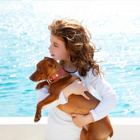 dog summer: brunette kid girl with dog on the sea view from a boat