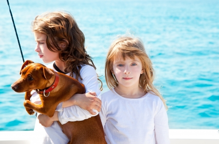 sister kid girls with dog mini pinscher on the sea view from a boat photo