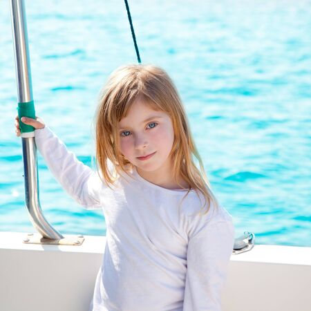 blond little kid girl sailing in a boat smiling at the sea photo