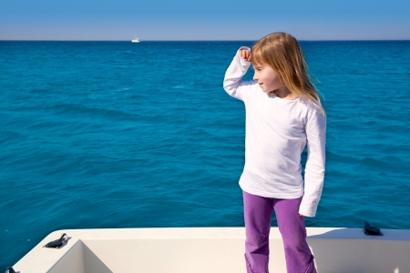 blond little kid girl sailing in a boat looking away at the sea photo
