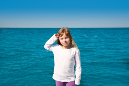 blond little kid girl sailing in a boat over the sea photo