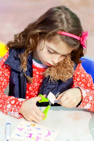 little kid girl working at school doing art work workshop  cutting with scissors photo